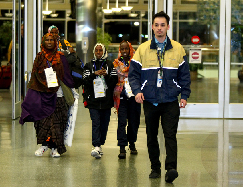 Somali refugees are escorted by a United Airlines representative as they arrive at the airport Feb. 13 in Boise, Idaho. The chairman of the U.S. bishops' migration committee sent a letter to the U.S. Department of Homeland Security and the U.S. Department of State urging dialogue on the U.S. Refugee Admissions Program.