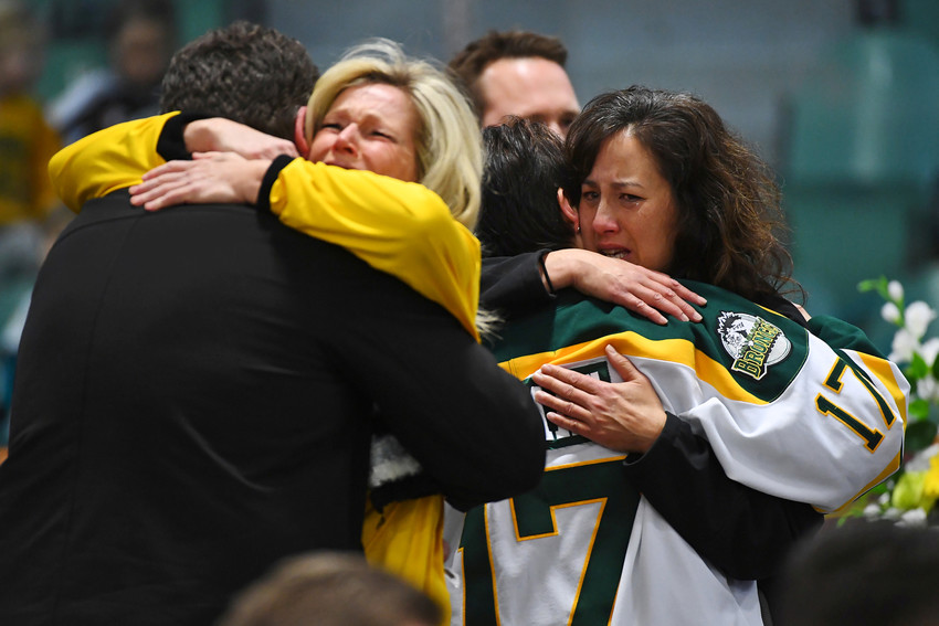 Mourners embrace during an April 8 vigil at Elgar Petersen Arena in Humboldt, Saskatchewan, to honor members of the Humboldt Broncos junior hockey team who were killed in a fatal bus accident.