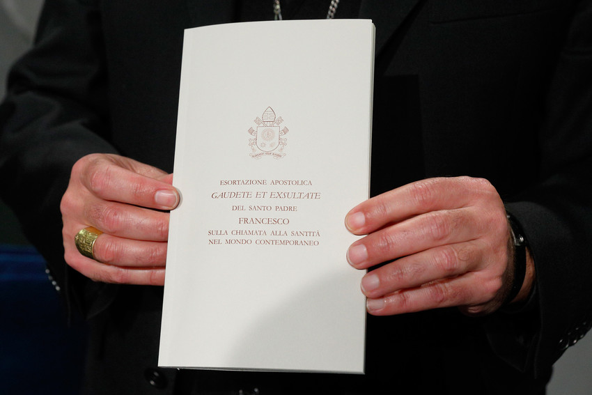 "Archbishop Angelo De Donatis, papal vicar for the Diocese of Rome, holds a copy of Pope Francis' exhortation, ""Gaudete et Exsultate"" (""Rejoice and Be Glad""), during a news conference on the exhortation at the Vatican April 9. The document is on the ""call to holiness in today's world."""