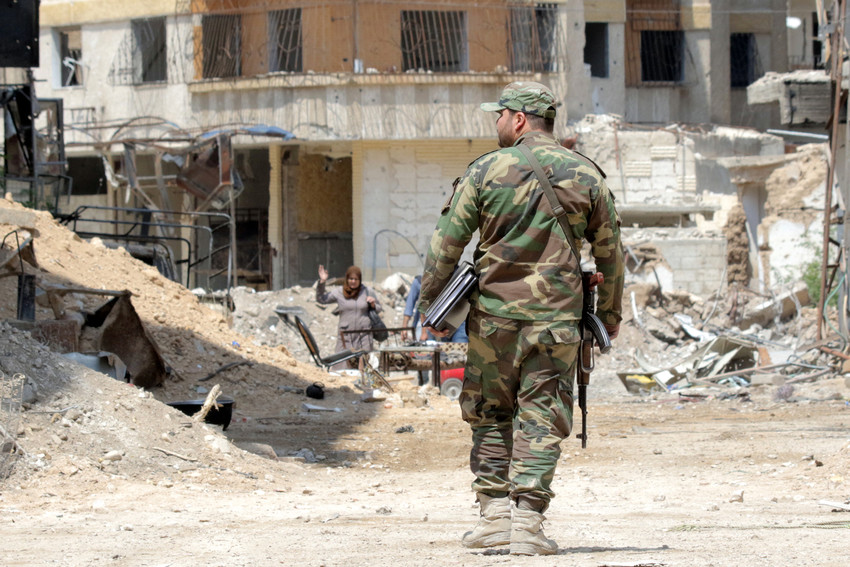A Syrian soldier walks amid destroyed buildings April 11 in the war-torn town of Ghouta. Lebanese Cardinal Bechara Rai appealed to world leaders to stop the war in Syria and to work for comprehensive peace through diplomatic means.