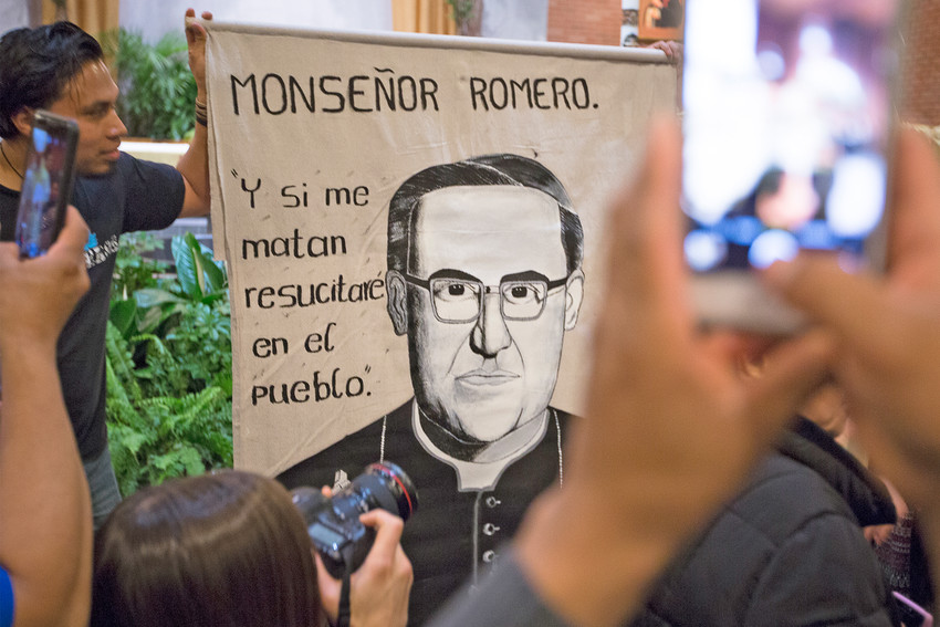 "People take sellfies of an image of Blessed Oscar Romero April 10 at St. Camillus Church in Silver Spring, Maryland. During an April 11 homily in Washington, Salvadoran Archbishop Jose Luis Escobar Alas said the canonization of Blessed Romero will ""probably"" be in Rome and ""probably"" take place at end of October after a meeting of bishops."