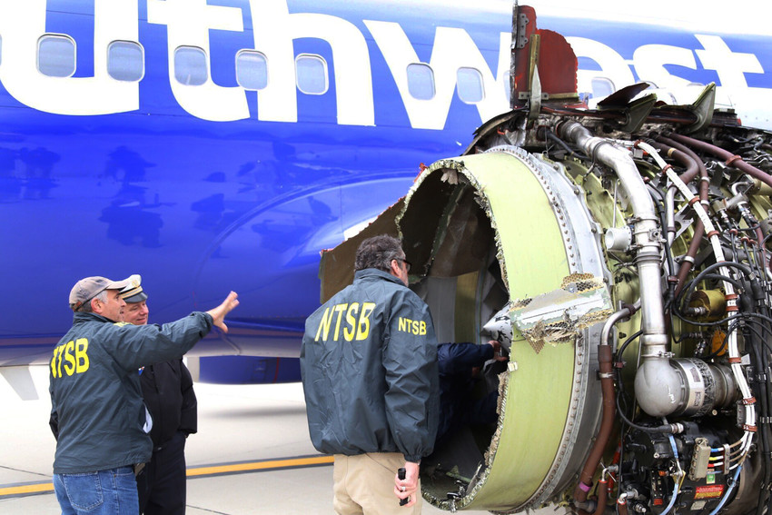 Investigators with the National Transportation Safety Board examine damage to the engine of a Southwest Airlines plane in Philadelphia April 17. Flight 1380 took off that morning from LaGuardia in New York, bound for Dallas, when the engine broke apart in midair and burst through a window, sucking passenger Jennifer Riordan partially out. She later died from her injuries. Riordan was a parishioner at Annunciation Catholic Church in Albuquerque, New Mexico, the Archdiocese of Santa Fe said in a statement.