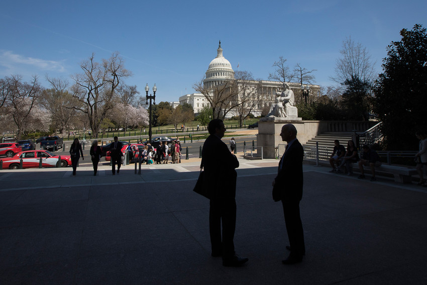 People stand near the U.S. Capitol in Washington April 13. U.S. bishops announced support April 25 for a bipartisan bill that provides a pathway to citizenship for young adults brought into the country as minors without legal documentation.