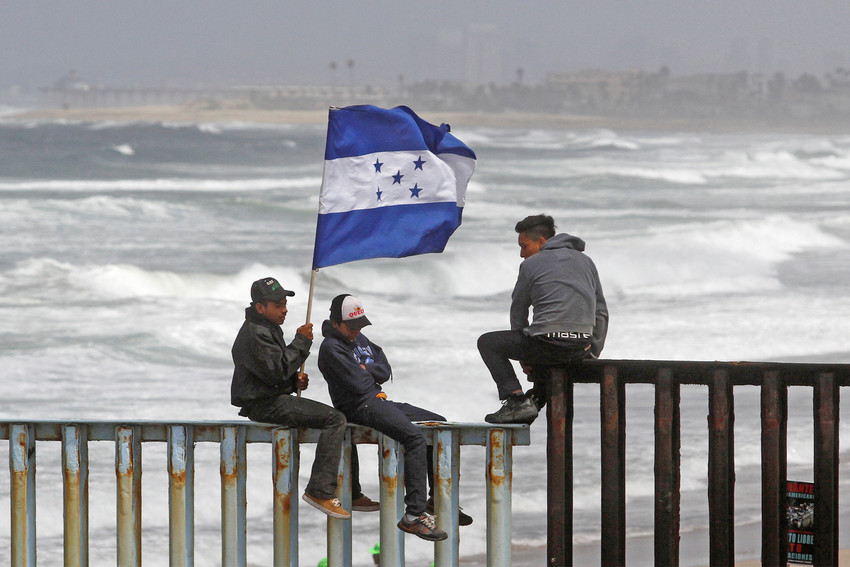People hold a Honduran flag while sitting on the border fence between Mexico and the United States in Tijuana, Mexico, April 29. The Trump administration was set to decide in early May whether Honduran holders of a special immigration status will be able to remain legally in the country.