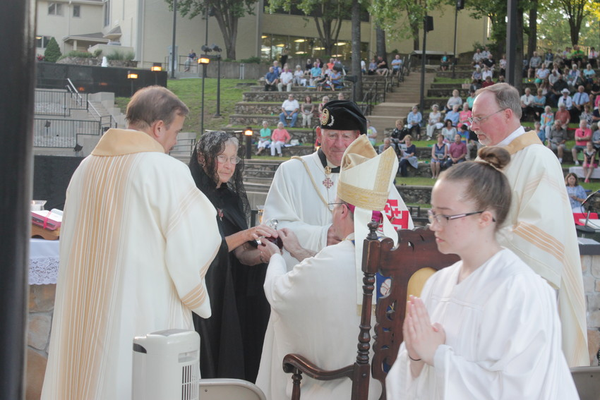 Wearing their regalia as members of the Equestrian Order of the Holy Sepulchre of Jerusalem, Don and Jo Ann Drake of St. Patrick parish in Laurie present to Bishop W. Shawn McKnight the bread and wine during the offertory at Mass in the National Shrine of Mary, Mother of the Church, in Laurie.