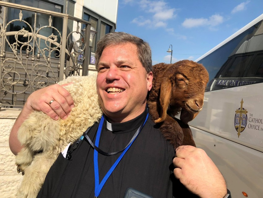 Fr. Oligschlaeger holds a lamb during his Holy Land pilgrimage.