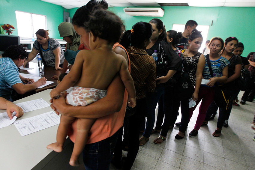 In this 2014 file photo, women and their children wait in line to register at the Honduran Center for Returned Migrants in San Pedro Sula after being deported from Mexico.
