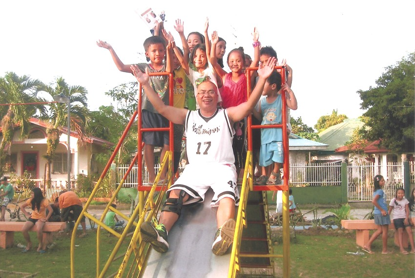 """Father Donardo """"Dandi"""" Bermejo, who served for almost a decade in the Jefferson City diocese, joins children of sugar plantation workers in trying-out a new playground he helped to get built in one of the communities he ministers to on his home island of Negros Occidental in the Philippines."""