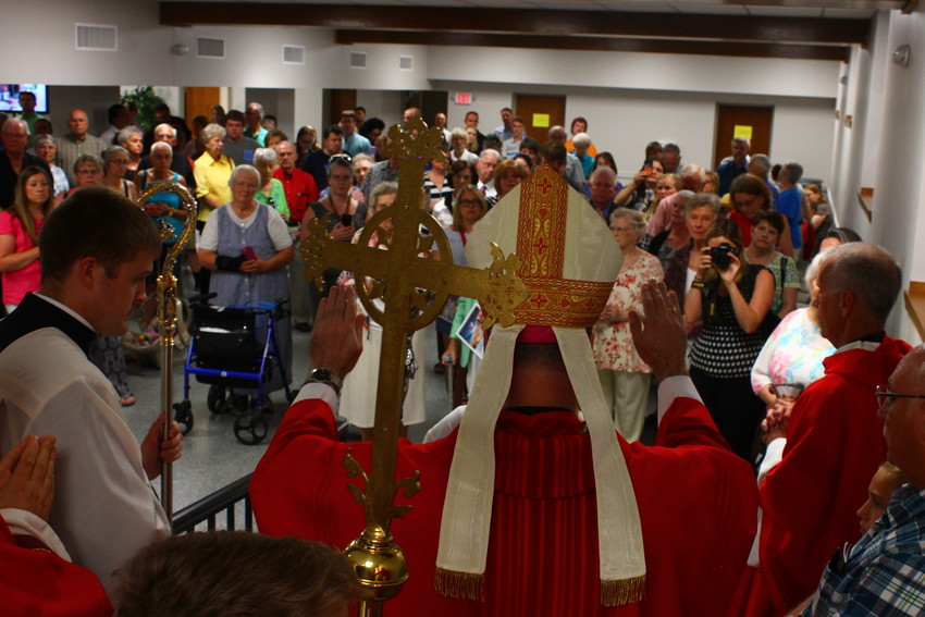 Bishop W. Shawn McKnight extends his hands while blessing the recently renovated Selinger Catholic Hospitality Centre at St. Peter in Jefferson City June 30.— Photo by Jay Nies