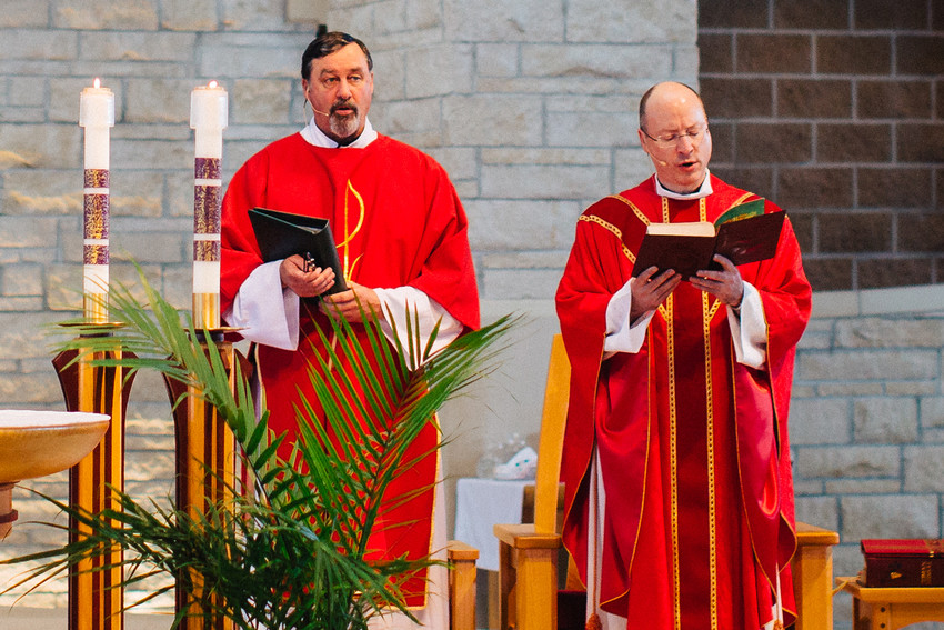 Deacon Jeff Jacobs assists Father (now Bishop) W. Shawn McKnight at Mass in Church of the Magdalen parish in Wichita on Palm Sunday in 2017.