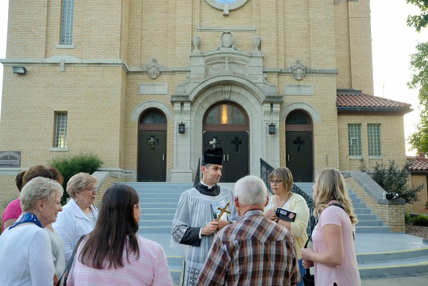"""Father Lawrence Carney jokes with people outside Ss. Peter and Paul Church in West Bend, Iowa, July 9. Earlier the """"walking priest,"""" as he is known gave a talk about his street evangelization as part of the parish's Grotto Speaker Series. A priest of the Diocese of Wichita., Kan, he is on loan to the Diocese of Kansas City-St. Joseph, Mo., where he is chaplain to the Benedictines of Mary, Queen of Apostles in Gower, Missouri."""