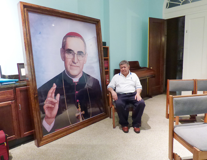 Marcelo Perdomo poses in front of large portrait of Blessed Oscar Romero Aug. 2 at the Shrine of the Sacred Heart in Washington. Perdomo worked as a sacristan for Blessed Romero in his native San Miguel, El Salvador, in the early 1960s.