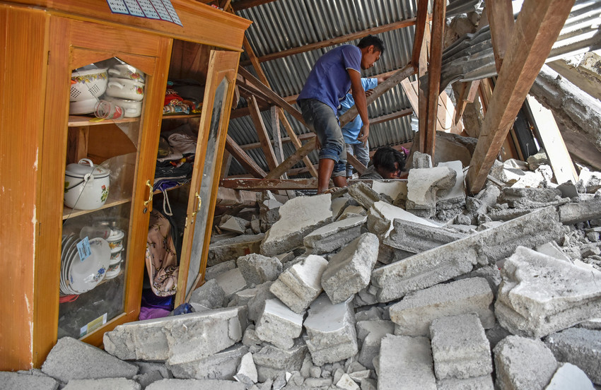 A villager walks through the ruins of a collapsed house July 29 following an earthquake on the island of Lombok in Indonesia. At least 16 people were killed and hundreds injured July 29 in the magnitude 6.4 earthquake.