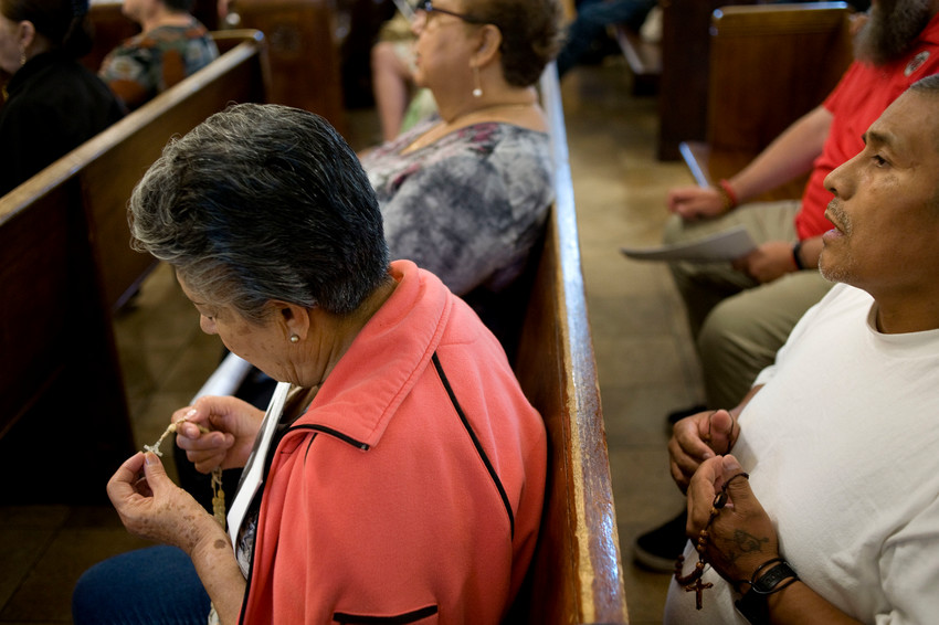Worshippers pray the rosary during a prayer service Sept. 7 at Dolores Mission Church in Los Angeles.