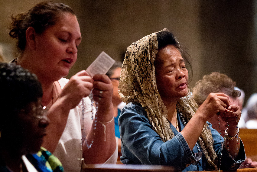 In this 2014 file photo, women pray the Rosary during the annual Global Rosary Relay for Priests in the Crypt Church at the Basilica of the National Shrine of the Immaculate Conception in Washington. Over the centuries, many Catholics of all walks of life have underscored the familial nature of praying the Rosary.