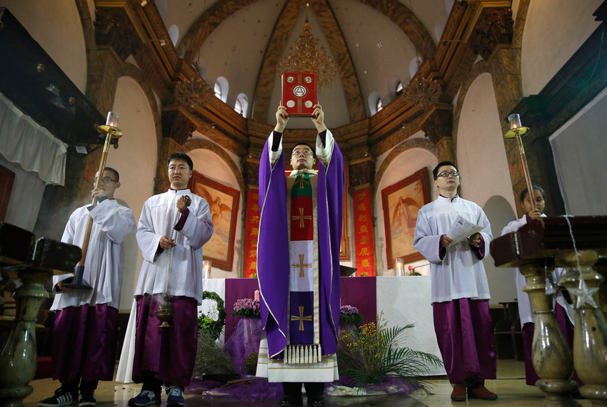 "A Catholic priest celebrates Sunday Mass in Beijing in this Dec. 4, 2016, file photo. In a special message addressed ""to the Catholics of China and to the universal Church,"" released by the Vatican Sept. 26, Pope Francis said he hoped a recent Sin-Vatican agreement would help ""restore full communion among all Chinese Catholics."""