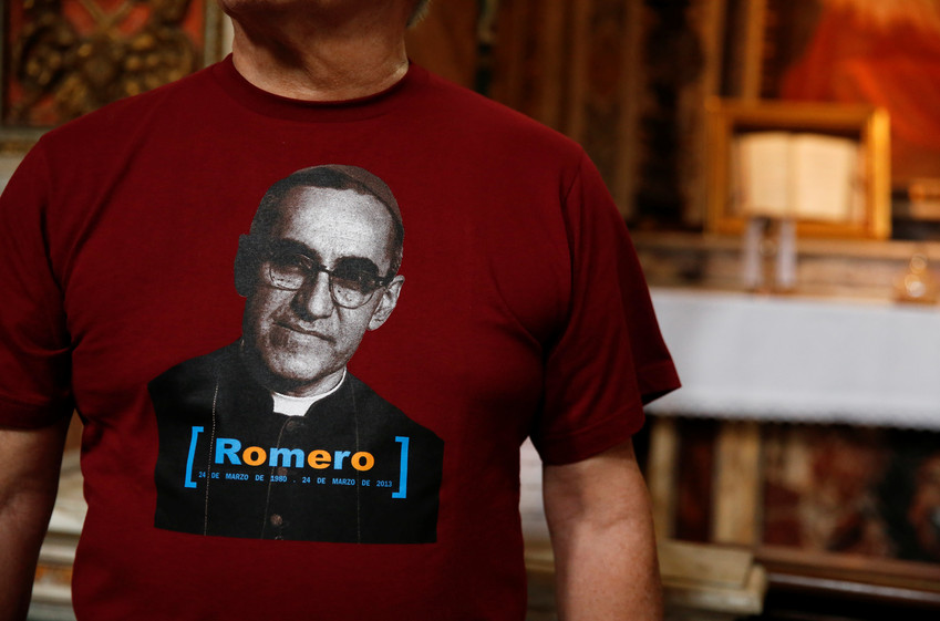A man in Rome wears a Blessed Oscar Romero T-shirt Oct. 11 while standing in front of a missal that belonged to the Salvadoran archbishop on exhibit in the Basilica of St. Bartholomew.