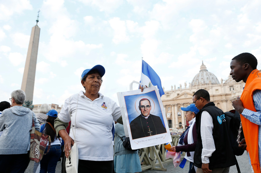 Milandro DeJesus holds a picture of St. Oscar Romero before Pope Francis' celebration of the canonization Mass for seven new saints in St. Peter's Square at the Vatican Oct. 14. Among the new saints are St. Paul VI and St. Oscar Romero.