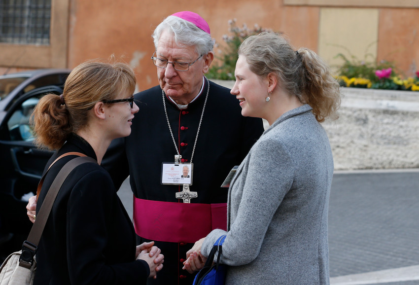 Bishop Lucas Van Looy of Gent, Belgium, introduces pre-synod delegate Anne Lien Boone, left, to synod delegate Marguerite-Marie Le Hodey of Belgium before a session of the Synod of Bishops on young people, the faith and vocational discernment at the Vatican Oct. 16.