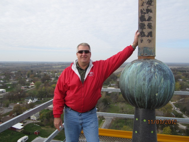Brad Copeland, diocesan director of buildings and properties, touches the 8-foot-tall cross atop the steeple of St. Joseph Church in Edina in this 2012 file photo.