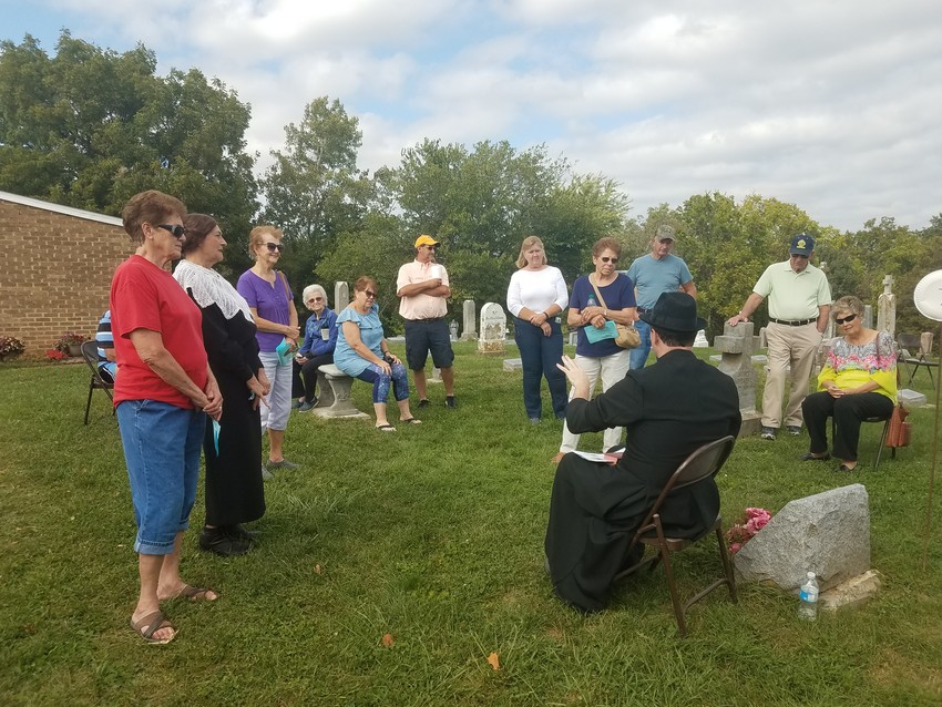 Participants in the Osage County Historical Society's 2018 Cemetery Walk in Our Lady Help of Christians Cemetery in Frankenstein listen to Father Daniel Merz portray the late Father George Fugel.