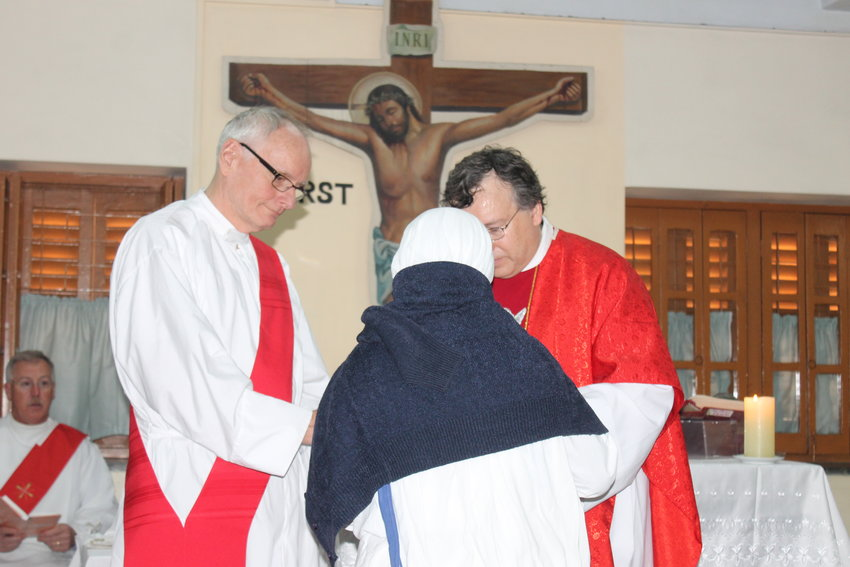 Deacon Alan D. Sims, left, assists Father Mark Smith during a Mass at the tomb of St. Teresa of Kolkata during a 2016 diocesan pilgrimage to India.
