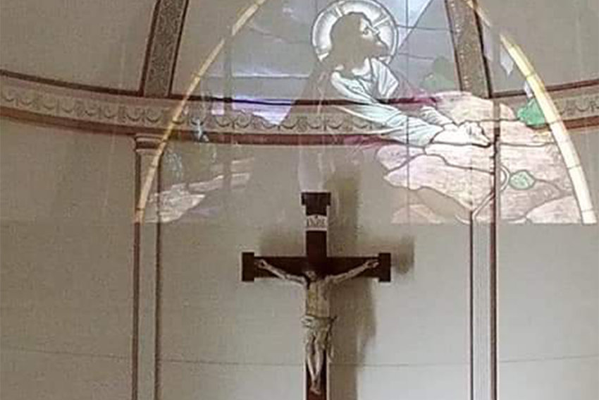 A stained-glass window depicting Jesus' agony in the garden the night before His crucifixion reflects on glass in the vestibule of St. Joseph Church in Edina, overlapping the crucifix in the sanctuary.