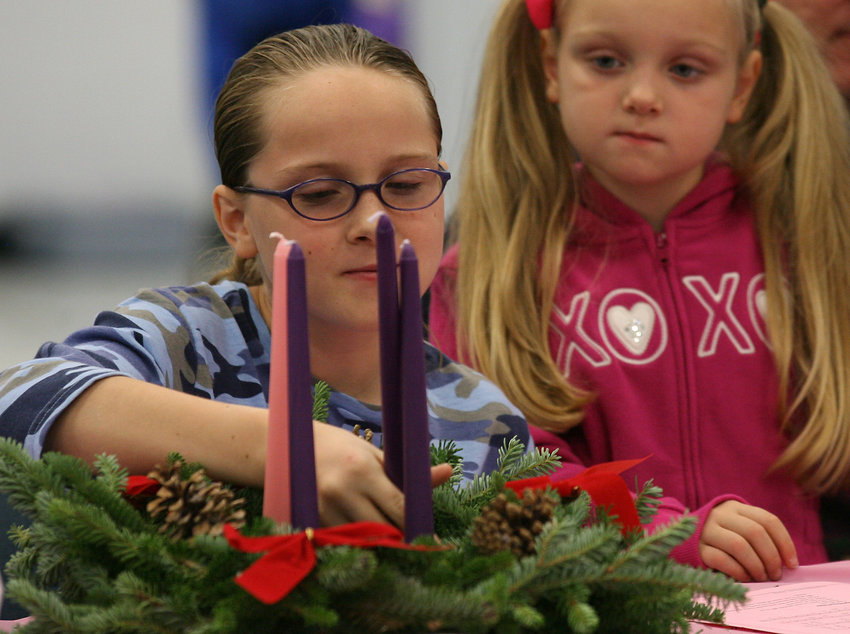 "A girl adjusts candles on an Advent wreath. ""Be watchful!"" and ""Be alert!"" are two traditional spiritual commands often heard by Catholics during the Advent season."