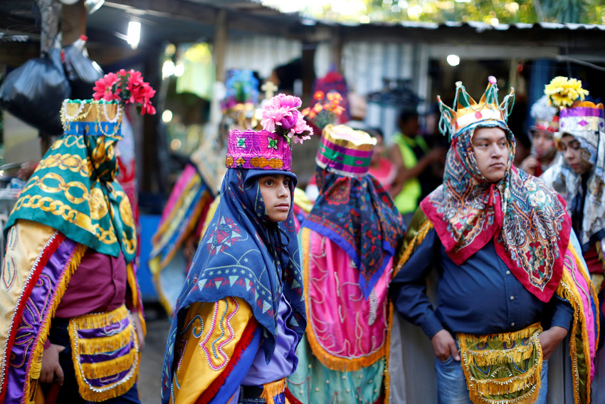 """Members of the traditional group of """"Los Historiantes"""" gather outside a house as they celebrate the feast of the Epiphany Jan. 6 in San Salvador, El Salvador."""