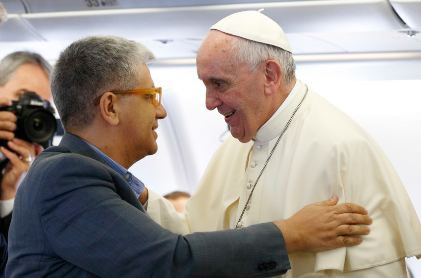 Pope Francis greets Italian journalist Andrea Tornielli aboard his flight from Rome to Quito, Ecuador, in this July 5, 2015, file photo.