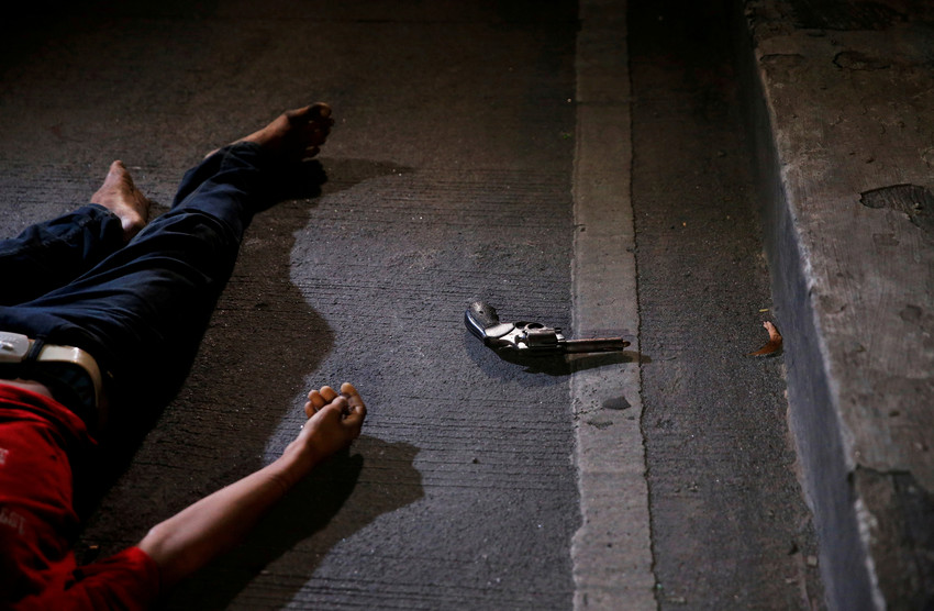 """A revolver is seen near the body of a man killed by police after drugs were found in his pockets in Manila, Philippines, Aug. 17, 2017. Catholic bishops in the Philippines broke what they described as their """"collective silence"""" over """"many disturbing issues"""" that have confronted the country in recent months."""