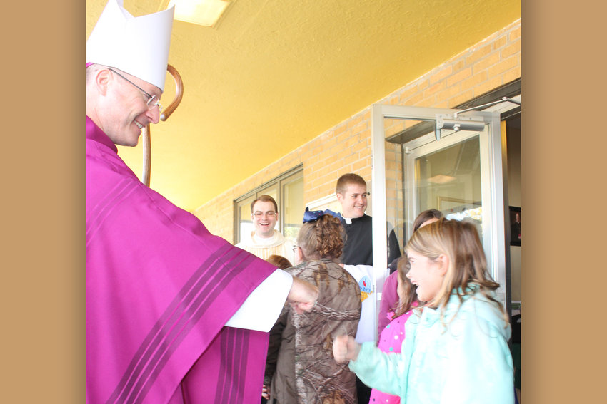 Bishop W. Shawn McKnight fist bumps with a student of St. Brendan School in Mexico after offering Mass in St. Brendan Church last fall.