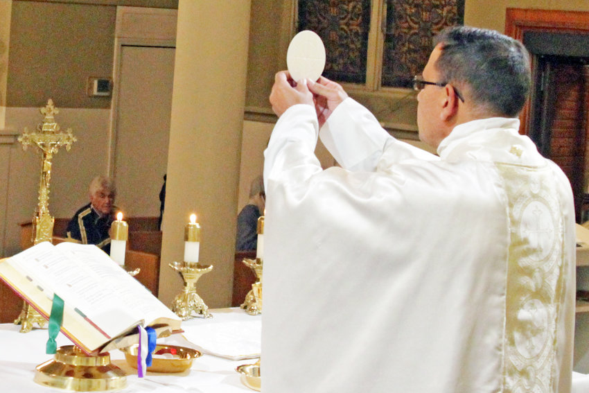 Fr. Anthony Viviano elevates the Eucharist at a Respect Life Mass in St. Joseph Church in Westphalia.