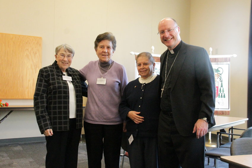 Sister Laura Magowan CCVI, Sister Bertha Flores CCVI and Sister Guadalupe Ruiz CCVI share a toast with Bishop W. Shawn McKnight during the diocesan celebration of World Day for Consecrated Life. The sisters' congregation, the Sisters of Charity of the Incarnate Word, is celebrating its 150th anniversary this year.