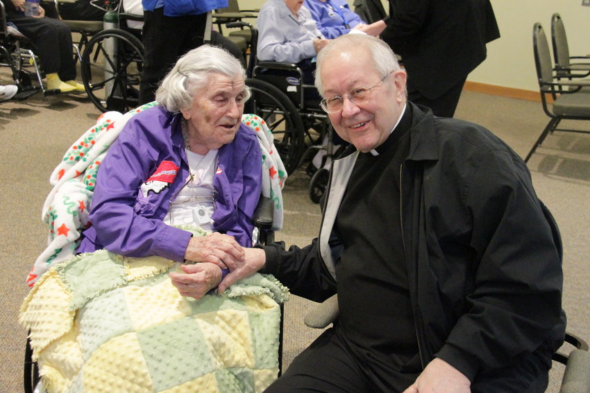 Bishop Emeritus John R. Gaydos visits with residents and visitors at St. Joseph's Bluffs in Jefferson City after offering Mass in the chapel there on Ash Wednesday.