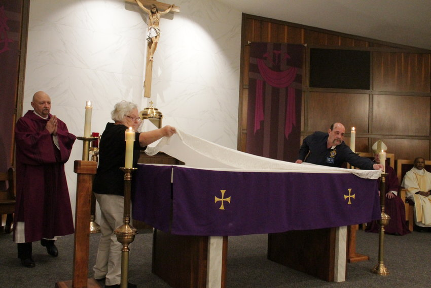 Members of Sacred Heart parish in Eldon place the altar cloth onto the altar of their newly renovated church during Mass with Bishop W. Shawn McKnight on March 9.
