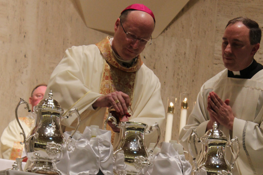 In this March 25, 2018, file photo, Bishop W. Shawn McKnight mixes the balsam with the Oil of Sacred Chrism during last year's Chrism Mass for the Jefferson City diocese.