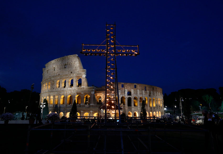 An illuminated cross is seen April 19, 2019, outside Rome's Colosseum before Pope Francis leads the Way of the Cross.