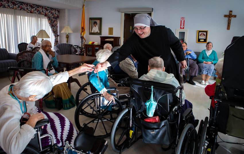 Sister Constance Veit, a Little Sister of the Poor, collects rosaries from elderly residents following prayers at the Jeanne Jugan Residence for senior care in Washington March 25, 2019. Sister Constance is considered a spiritual mother by many of the residents, who said they will honor her on Mother's Day. (CNS photo/Chaz Muth) See MOTHERS-DAY-NUN April 26, 2019.