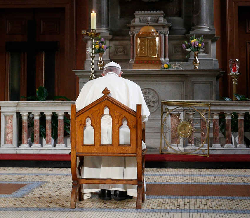 Pope Francis prays in front of a candle in memory of victims of sexual abuse as he visits St. Mary's Pro-Cathedral in Dublin Aug. 25, 2018. Pope Francis has revised and clarified norms and procedures for holding bishops and religious superiors accountable in protecting minors as well as in protecting members of religious orders and seminarians from abuse.