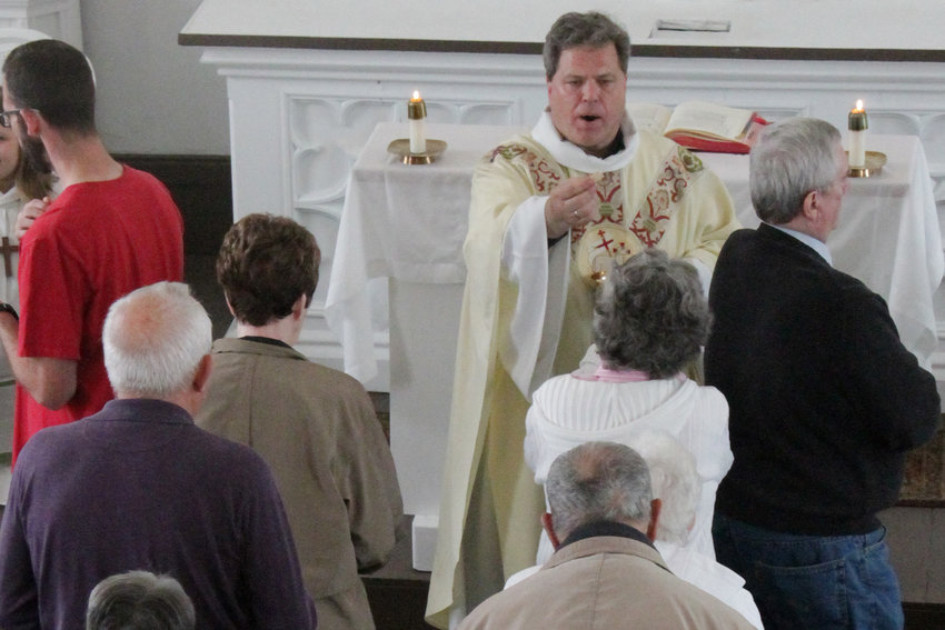 Father Gregory Oligschlaeger distributes Holy Communion April 28 during Mass in St. Peter Church in Brush Creek.