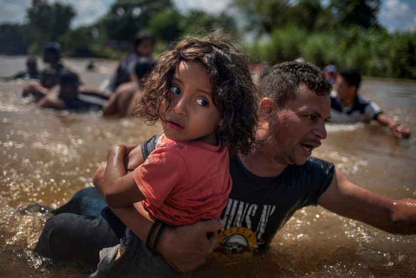 Honduran migrant Luis Acosta carries 5-year-old Angel Jesus through the Suchiate River near Tapachula, Mexico, Oct. 29, 2018.