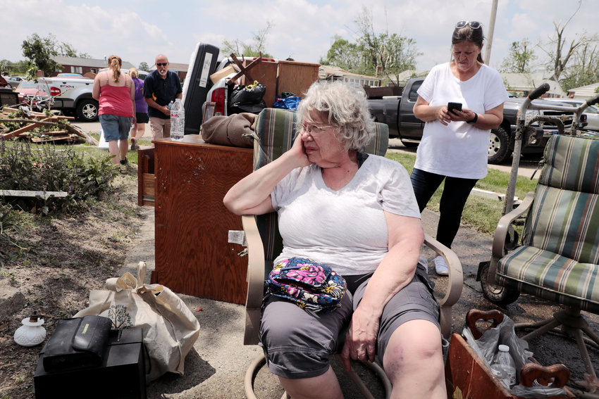 Sue Taulbee, 71, watches as her family works to collect memorabilia from her damaged house May 28, 2019, after a tornado touched down overnight in Brookville, Ohio. On May 27, the massive tornado tore through Dayton, one of Ohio's largest cities, leveling homes, entire apartment complexes, knocking out power and water to tens of thousands of people in the city and surrounding suburbs, including Brookville. Queen of Martyrs Catholic Church in Dayton also sustained significant damage in the storm.