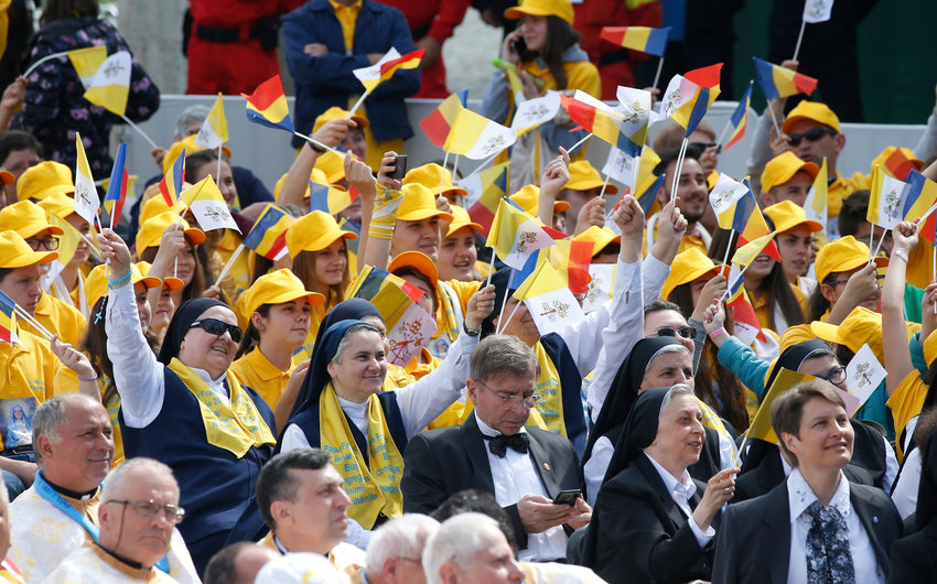 People wave the flags of the Vatican and Romania before Pope Francis' celebration of a Divine Liturgy and the beatification of seven martyred bishops of the Eastern-rite Romanian Catholic Church at Liberty Field in Blaj, Romania, June 2, 2019.