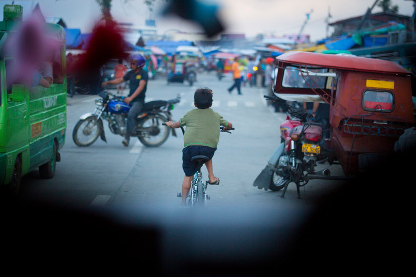 In this 2014 file photo, a boy rides his bike in the streets of Tacloban, Philippines. Darwin Ramos, a Filipino teenager who died in 2012 at the age of 17, could be on his way to sainthood after the Vatican declared him a Servant of God in March.