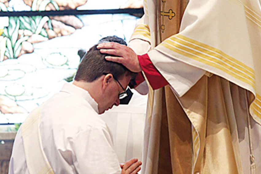 Bishop James V. Johnston Jr. of Kansas City-St. Joseph imposes hands upon Father Kendall Ketterlin at his priestly ordination on May 25 at the Cathedral of the Immaculate Conception in Kansas City.
