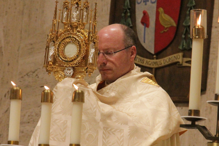 Bishop W. Shawn McKnight elevates the Most Blessed Sacrament during Benediction as part of the celebration of his 25th priestly anniversary, on June 2 in the Cathedral of St. Joseph.
