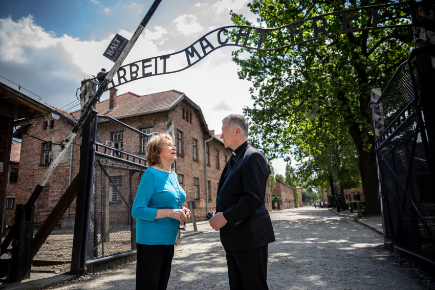 Fritzie Fritzshall, president of the Illinois Holocaust Museum and Education Center in Skokie, Ill., and survivor of the Auschwitz Nazi concentration camp, and Chicago Cardinal Blase J. Cupich, talk underneath the entrance gate at the camp in Oswiecim, Poland, July 4, 2019.