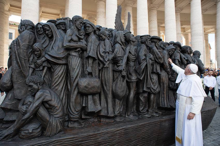 "Pope Francis attends the unveiling of a large bronze statue titled, ""Angels Unawares,"" by Canadian artist Timothy Schmalz, in St. Peter's Square at the Vatican Sept. 29, 2019. The statue depicts a group of migrants and refugees on a boat."