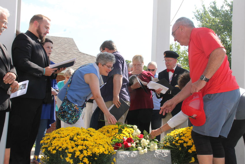 People who took part in a local observance of the National Day of Remembrance for the Aborted place flowers on the stone Memorial to the Unborn outside St. Andrew Church in Holts Summit
